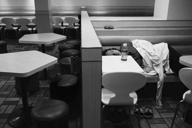A man sleeps at a 24-hour McDonald's restaurant in Hong Kong, China November 10, 2015. A large number of homeless people sleeping on the street has long been been a problem in Hong Kong mainly due to its high rent and soaring property. In recent years, McDonald's 24-hour fast food shops opening all over the city have become popular alternatives for people, know as McRefugees or McSleepers, to spend the night in a safer and more comfortable way than on the street. Picture taken on November 10, 2015. REUTERS/Tyrone Siu - RTS6EXQ