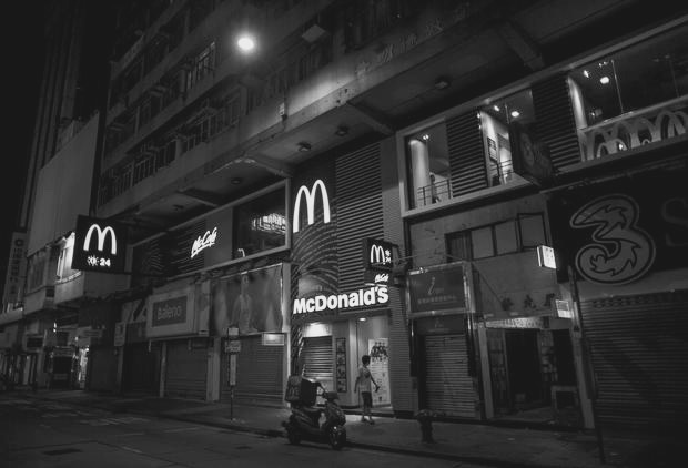 man walks past at a 24-hour McDonald's restaurant in Hong Kong, China November 10, 2015. A large number of homeless people sleeping on the street has long been been a problem in Hong Kong mainly due to its high rent and soaring property. In recent years, McDonald's 24-hour fast food shops opening all over the city have become popular alternatives for people, know as McRefugees or McSleepers, to spend the night in a safer and more comfortable way than on the street. Picture taken on November 10, 2015. REUTERS/Tyrone Siu - RTS6F1C