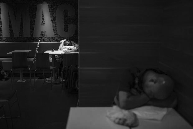 Men sleep at a 24-hour McDonald's restaurant in Hong Kong, China November 11, 2015. A large number of homeless people sleeping on the street has long been been a problem in Hong Kong mainly due to its high rents and soaring property prices. In recent years, the opening of McDonald's 24-hour fast food restaurants all over the city have become popular alternatives for homeless people known as McRefugees or McSleepers to spend the night in a safer and more comfortable way than on the street. REUTERS/Tyrone Siu - RTS6EZX
