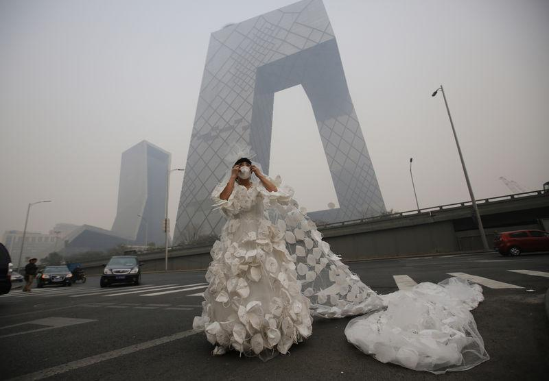 Kong Ning wears a wedding dress decorated with 999 face masks for her performance art work 'Marry the blue sky' as she poses for a photograph in front of the China Central Television (CCTV) Headquarters on a hazy day in Beijing November 19, 2014. Wearing a 10 meter-long wedding dress decorated with face masks is a part of Kong Ning's performance art work which signifies her frustration with air pollution. REUTERS/Kim Kyung-Hoon