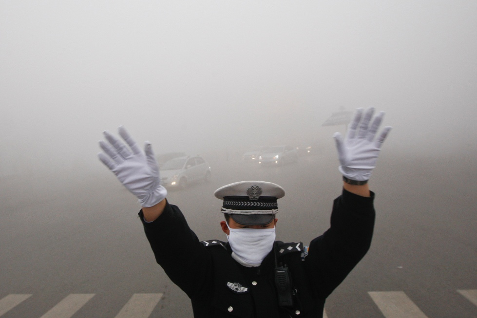 A traffic policeman signals to drivers during a smoggy day in Harbin, Heilongjiang province, October 21, 2013. The second day of heavy smog with a PM 2.5 index has forced the closure of schools and highways, exceeding 500 micrograms per cubic meter on Monday morning in downtown Harbin, according to Xinhua News Agency. REUTERS/China Daily (CHINA - Tags: ENVIRONMENT TRANSPORT) CHINA OUT. NO COMMERCIAL OR EDITORIAL SALES IN CHINA - RTX14IFX