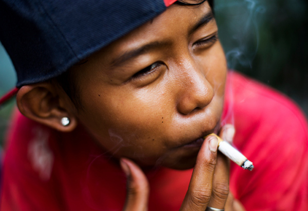 "Ompong, which means ""toothless"" in Bahasa, poses for a photograph as he has a cigarette in South Jakarta, Indonesia on February 14, 2014."