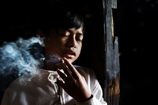 Illham Muhamad, who has smoked since he was five years old, poses for a photo as he slowly inhales his first cigarette of the day at his grandmother's home in Indonesia on February 10, 2014. He does not attend school and if his grandmother refuses to give him money to buy cigarettes he will cry and throw fits.
