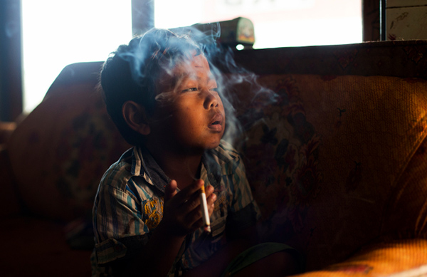 Dihan Muhamad, who used to smoke up to two packs of cigarettes a day before cutting down, poses for a photo as he smokes in his home in a village near the town of Garut, Indonesia on February 10, 2014.