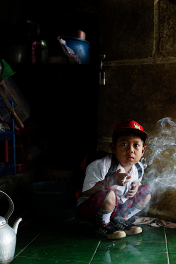Dihan Muhamad, who used to smoke up to two packs of cigarettes a day before cutting down, poses for a photo as he has his first cigarette at 7AM at his home before he attends his first grade class in his village near the town of Garut, Indonesia on February 10, 2014.