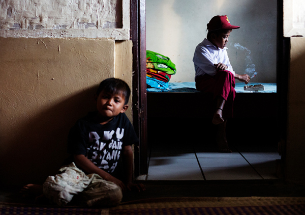 Ilham Hadi, who has smoked up to packs a day and began when he was four years old, poses for a photo wearing his third grade uniform while smoking in his bedroom as his younger brother looks on in their village near the town of Sukabumi, Indonesia on February 14, 2014.