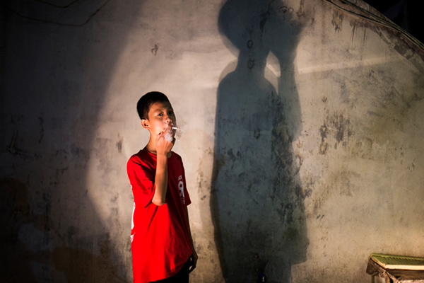 Andika Prasetyo, who smokes about a pack a day, has a cigarette outside an internet cafe where children are smoking inside in Depok, West Java, Indonesia on February 15, 2014.