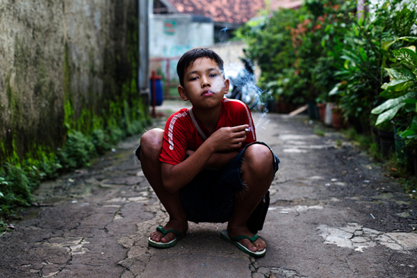 Rian, who smokes occasionally, poses for a photo as he smokes a cigarette in east Jakarta, Indonesia on February 12, 2014.