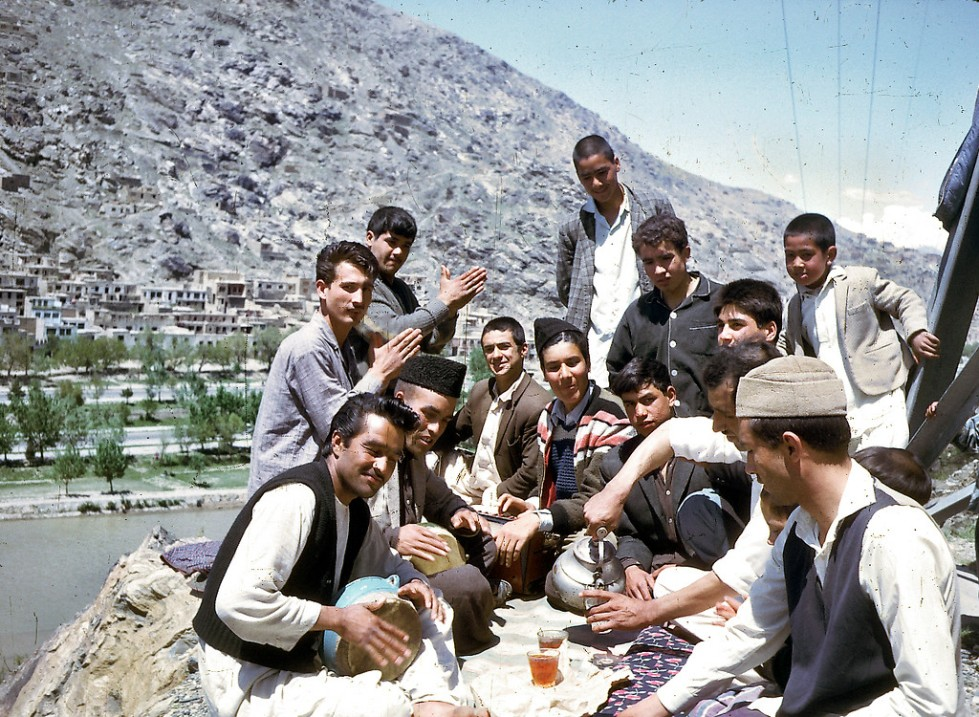 """A group of young Afghans share tea and music."""