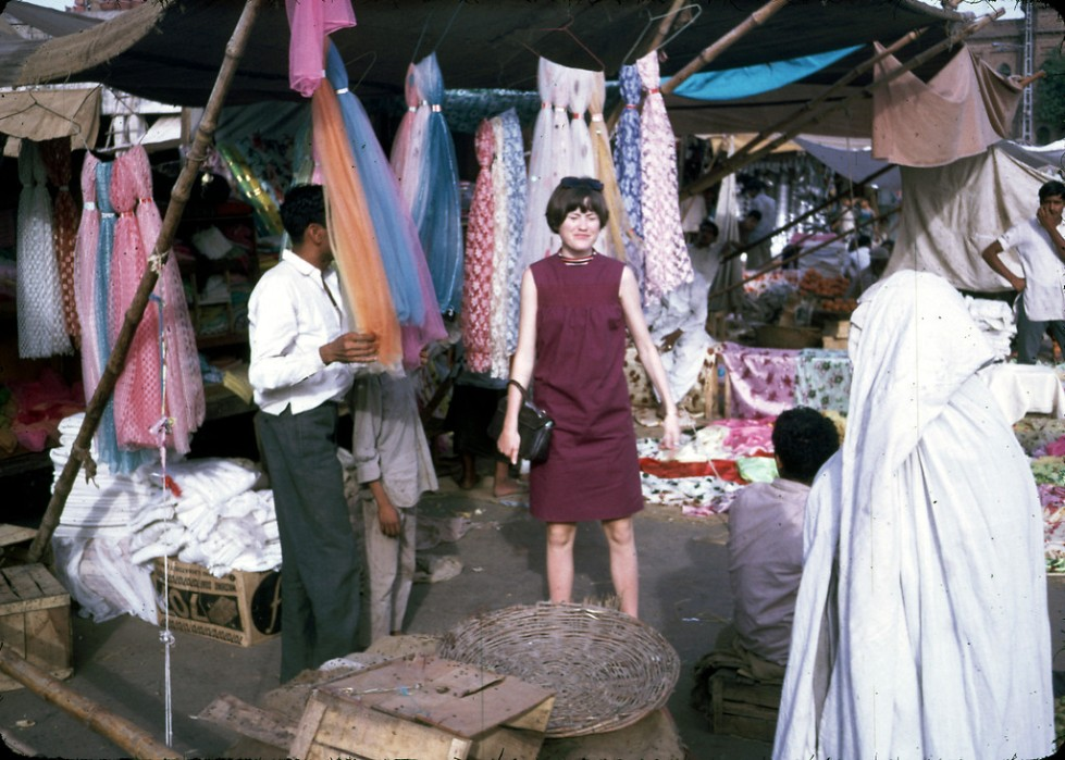 """Jan Podlich on a shopping trip in Istalif. Jan in a short, sleeveless dress and the woman to the right in a chadri (burka). We arrived in Kabul one sunshiny morning in June... My dad met us and was able to whisk us through the customs. We proceeded into Kabul in a UN ÒkombiÓ (kind of an old school SUV). I was tired, but I can remember being amazed at the sight of colorful (dark blue, green and maroon) ÒghostsÓ that were wafting along the side of the road. My dad explained there were women underneath those chadris, and that some women had to wear them out in public. We never called the garments Òburkas.Ó Depending on the country, women practicing purdah (Islamic custom requiring women to cover up) wear different styles of coverings, which have different names."" - Peg Podlich. """