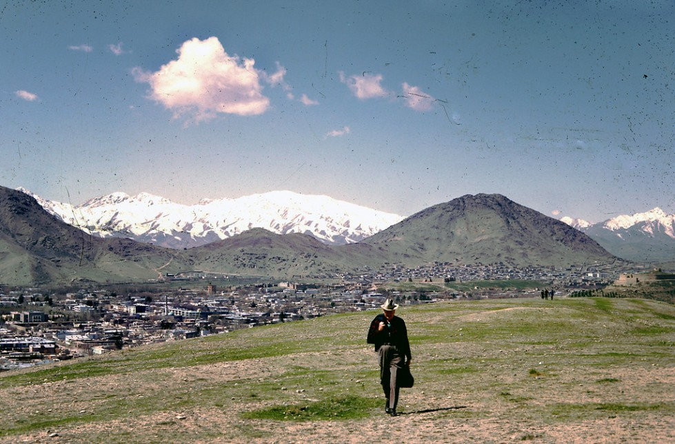 """Dr. Bill Podlich on a hillside in Kabul. ""My dad was a professor of Elementary Education, specializing in teaching Social Studies, at Arizona State University in Tempe, Arizona from 1949 until he retired in 1981. He had always said that since he had served in WWII (he trained soldiers against chemical warfare), he wanted to serve in the cause of peace. In 1967, he was hired by UNESCO as an Expert on Principles of Education, for a two-year stint in Kabul, Afghanistan at the Higher TeachersÕ College. Throughout his adult life, because he was interested in social studies, whenever he traveled around (in Arizona, to Mexico and other places), he continued to take pictures. In Afghanistan he took half-frame color slides (on Kodachrome), and I believe he used a small Olympus camera."" - Peg Podlich."""